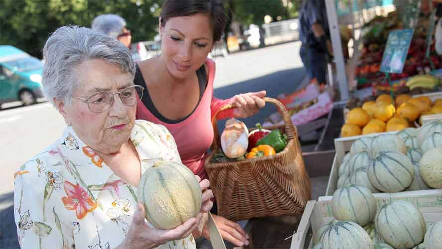 Elderly woman inspecting a melon at a farmer's market