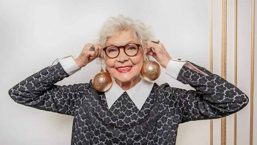 Smiling senior woman with black glasses, holding two gold Christmas baubles up as earrings