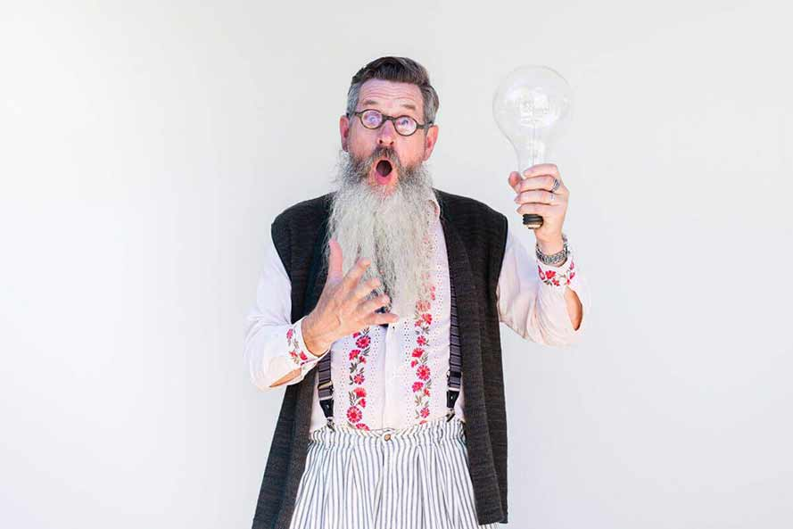 Senior bearded man holding a giant lightbulb