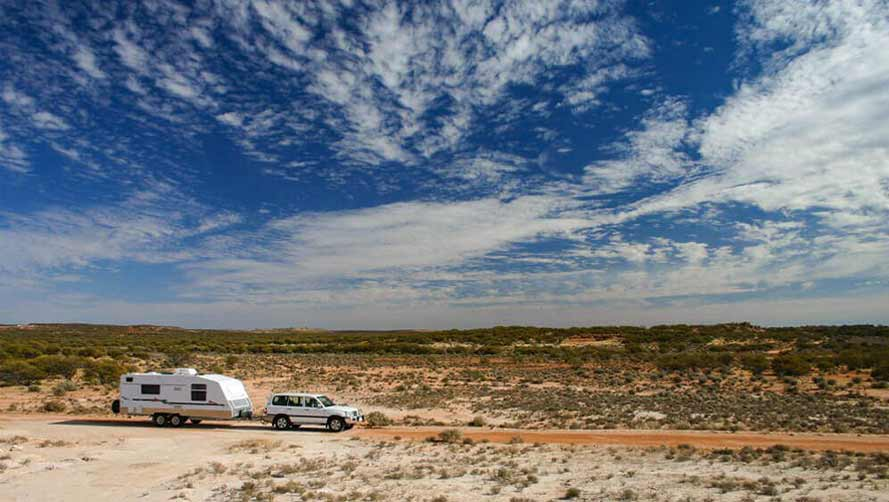 Large 4WD towing caravan across Australian outback