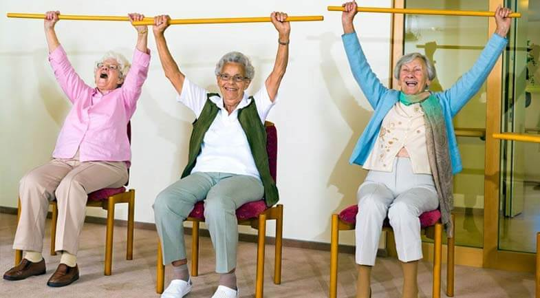 3 elderly women with their arms in the air