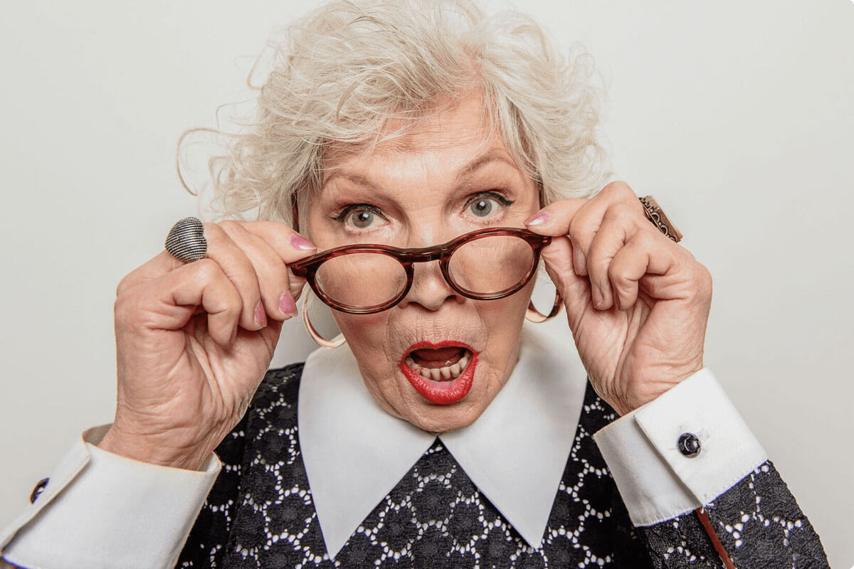 Quirky older woman adjusting her glasses