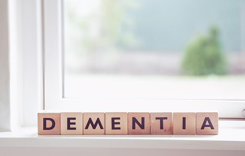 Wooden blocks spelling out dementia, sitting on a sunlit windowsill