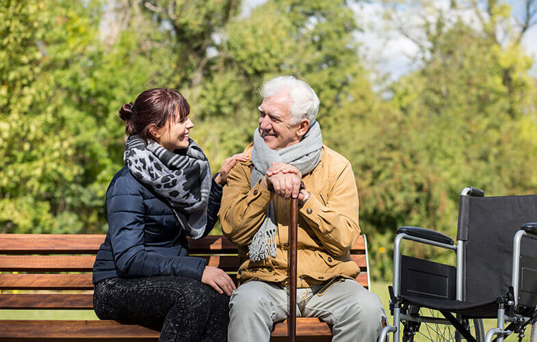 Smiling senior man sitting on park bench with a carer