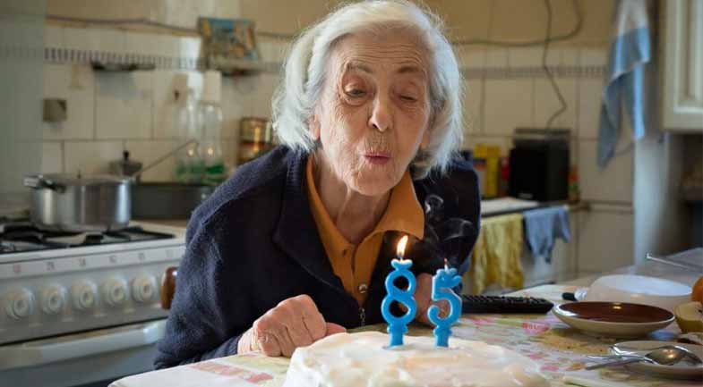 Older woman blowing out her 85th birthday cake candles