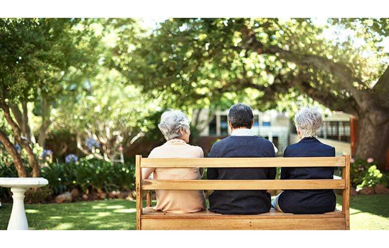 3 seniors sitting on a park bench with backs to camera