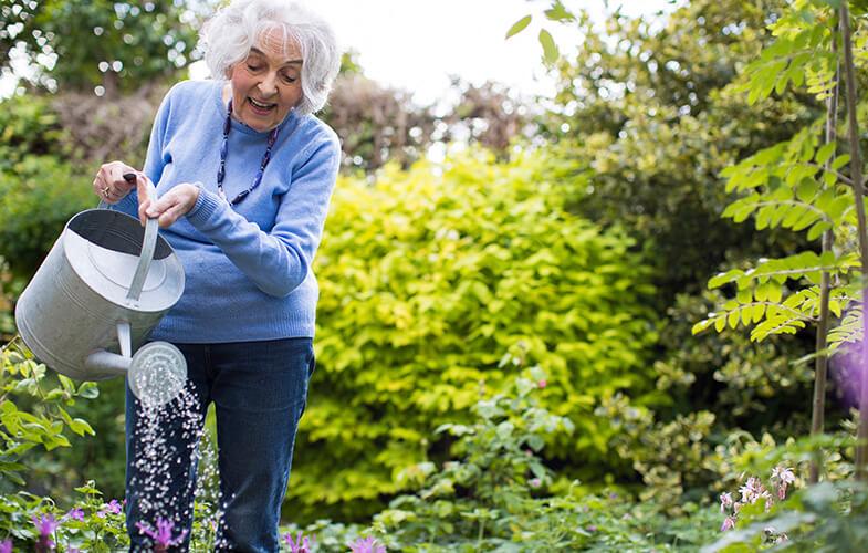 Senior-Woman-Watering-Flowers-In-Garden
