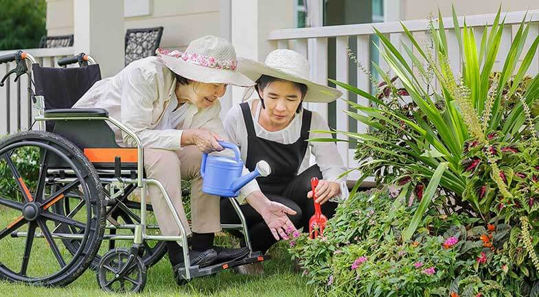 Woman in a wheelchair with a friend doing some gardening
