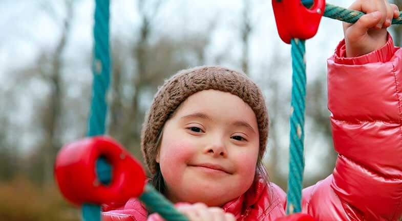 A smiling young girl with Downs Syndrome plays on a swing