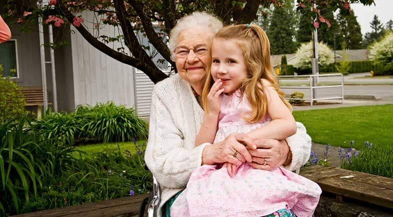 Happy senior woman with little girl on her lap