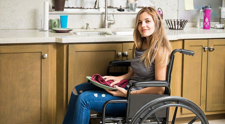 Young girl in a wheelchair drying a plate