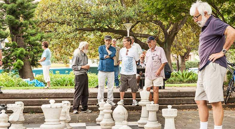 Group of senior men playing giant outdoor chess