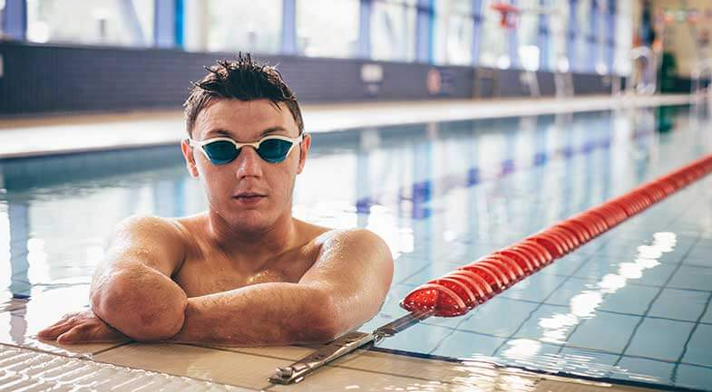 Young man with amputated forearm wearing goggles in a swimming pool