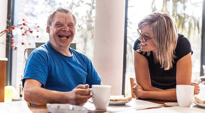 A disabled man and his support worker share a cup of tea