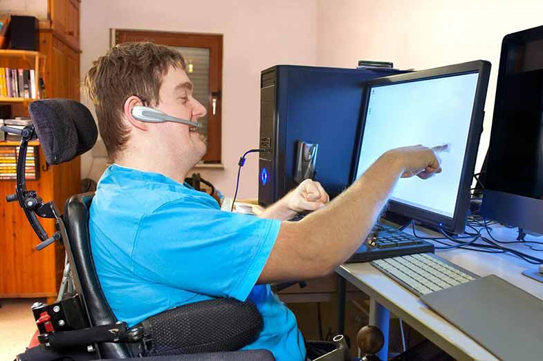 Disabled man in a wheelchair using his computer