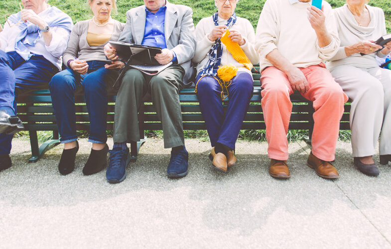 A group of seniors sitting on a parkbench