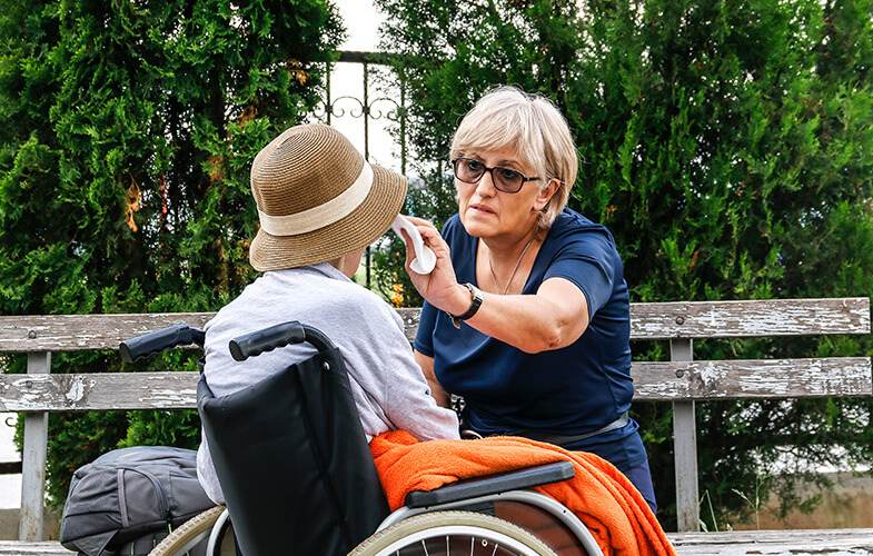 Middle-aged woman wiping the face of an elderly person in a wheelchair