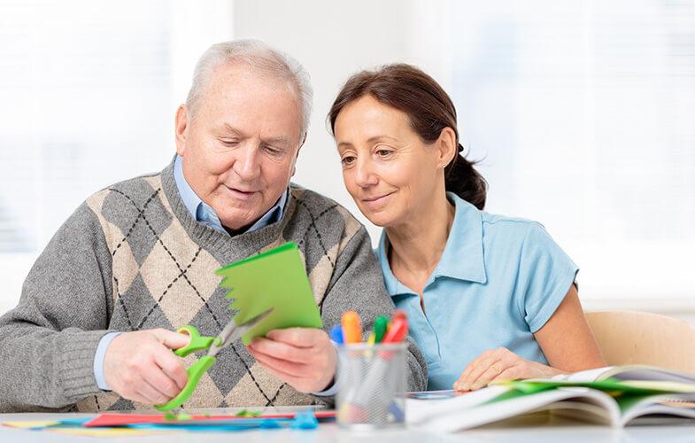 Senior-man-cutting-paper-with-scissors