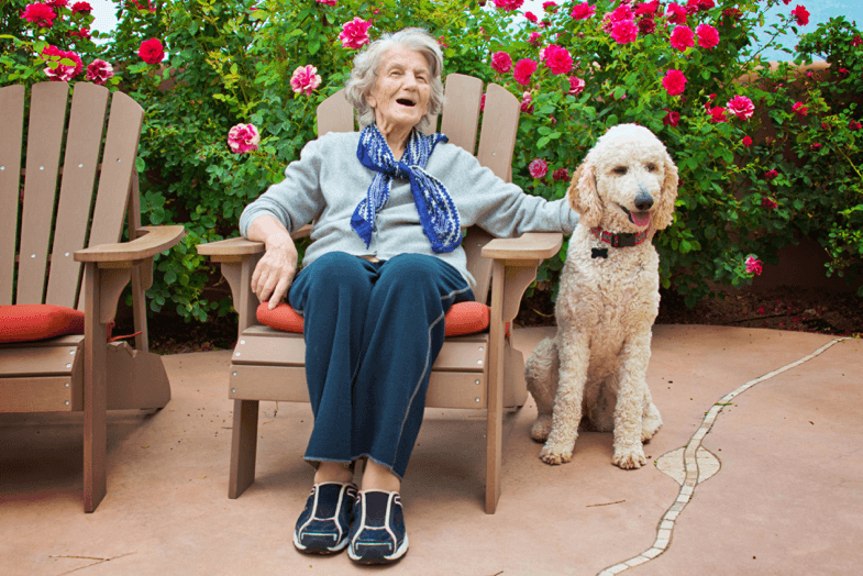 Older woman sitting with her dog in a garden chair