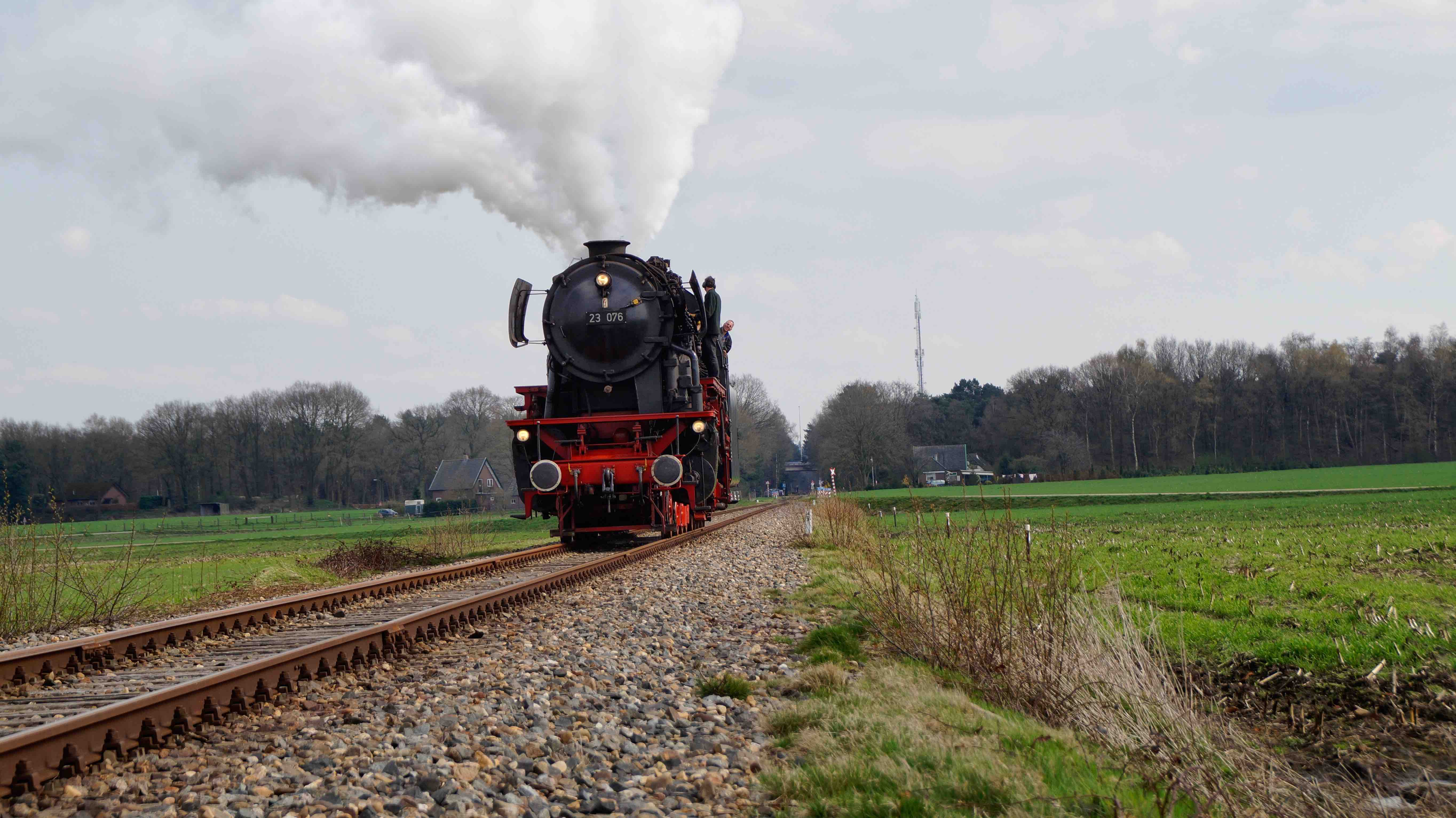 A black and red steam train on a country railway