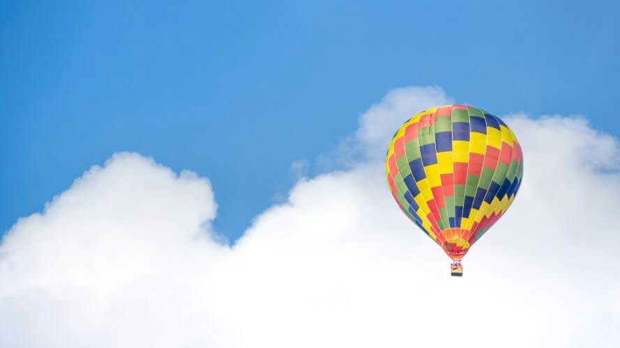 Brightly coloured hot air balloon against blue sky