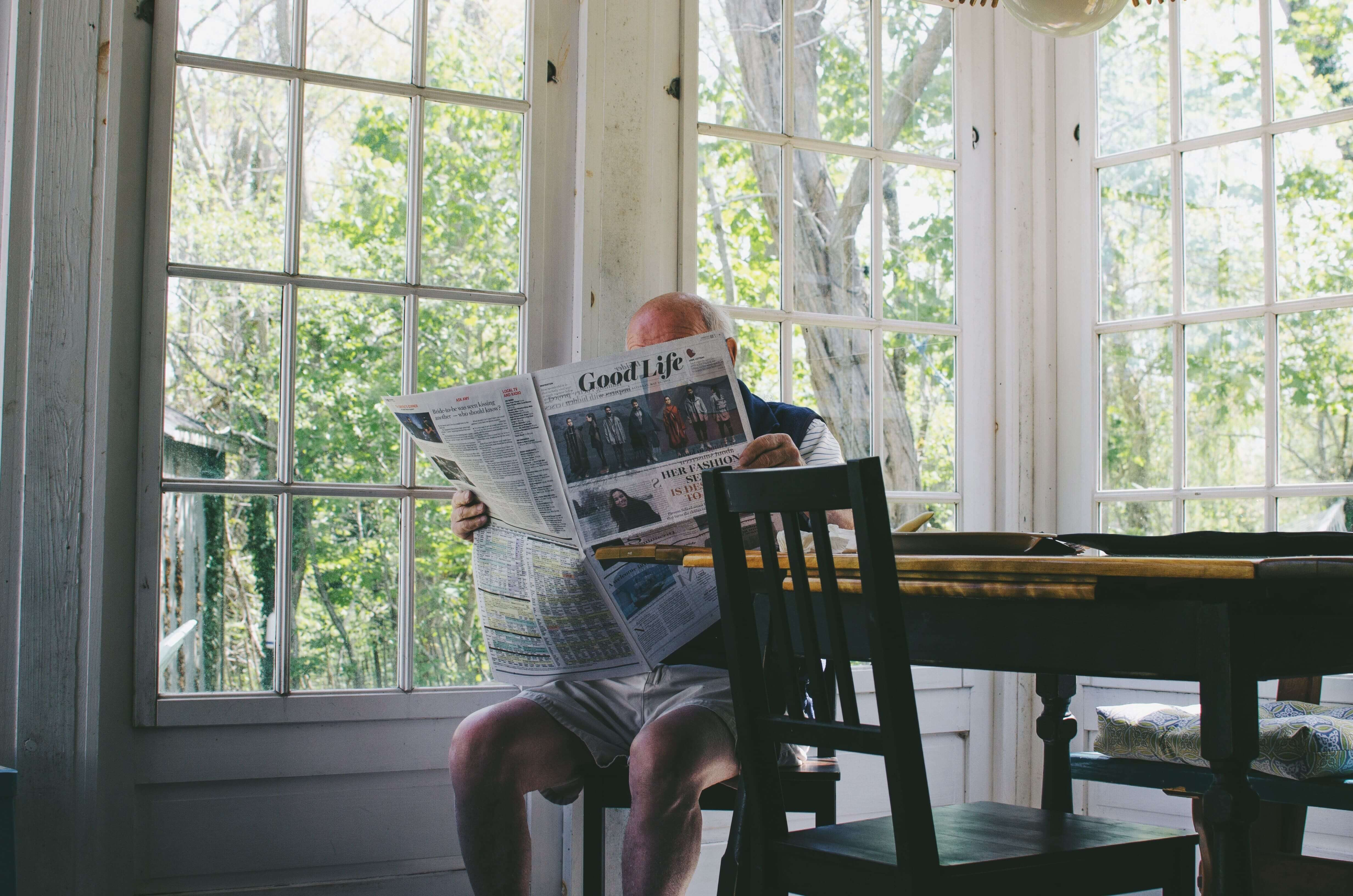 Senior man reading newspaper in brightly lit dining room
