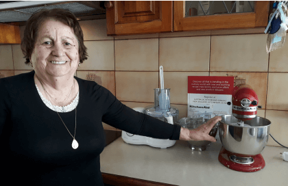Older woman in kitchen with KitchenAid mixer