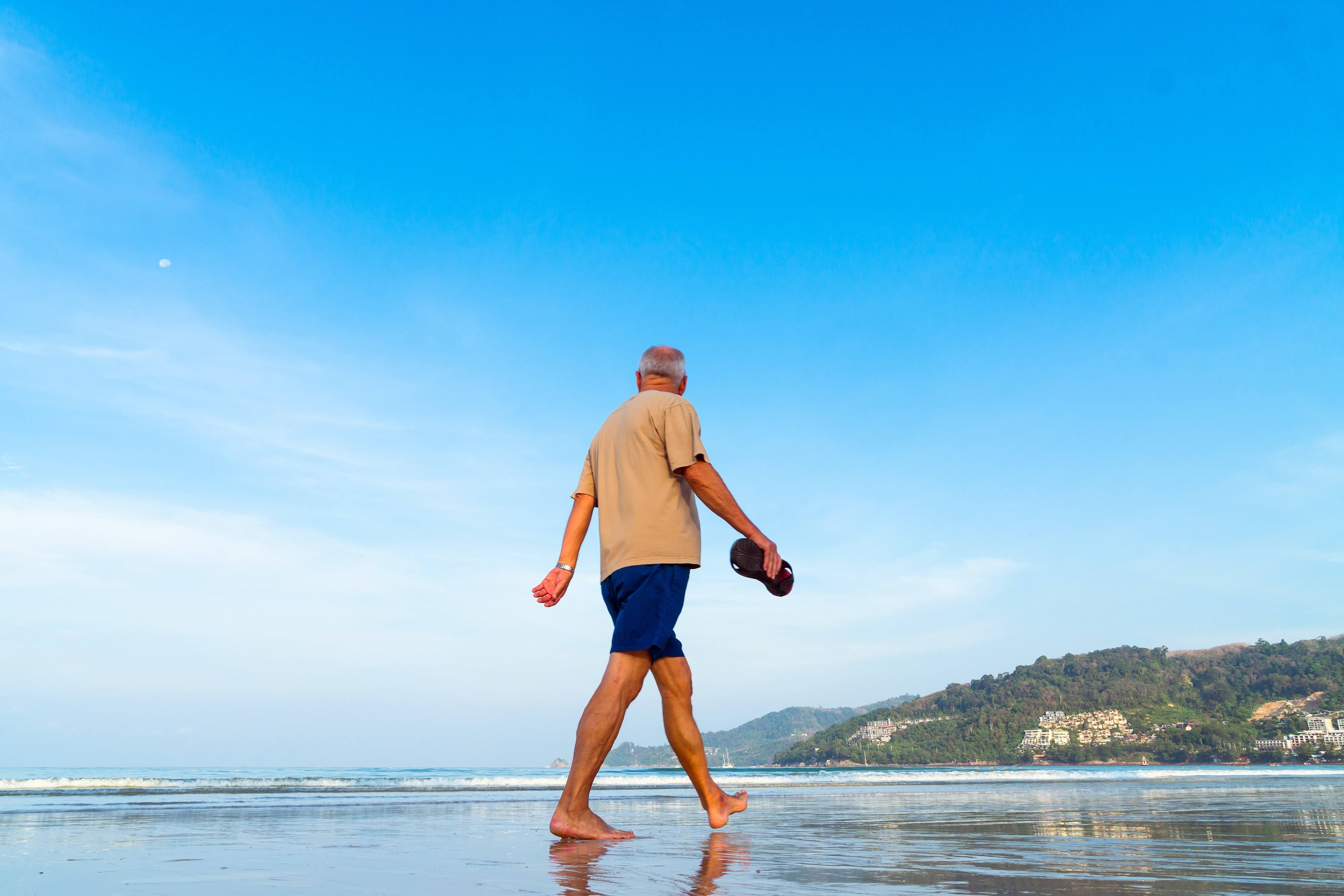 Senior man walking on the beach with flip flops in his hand
