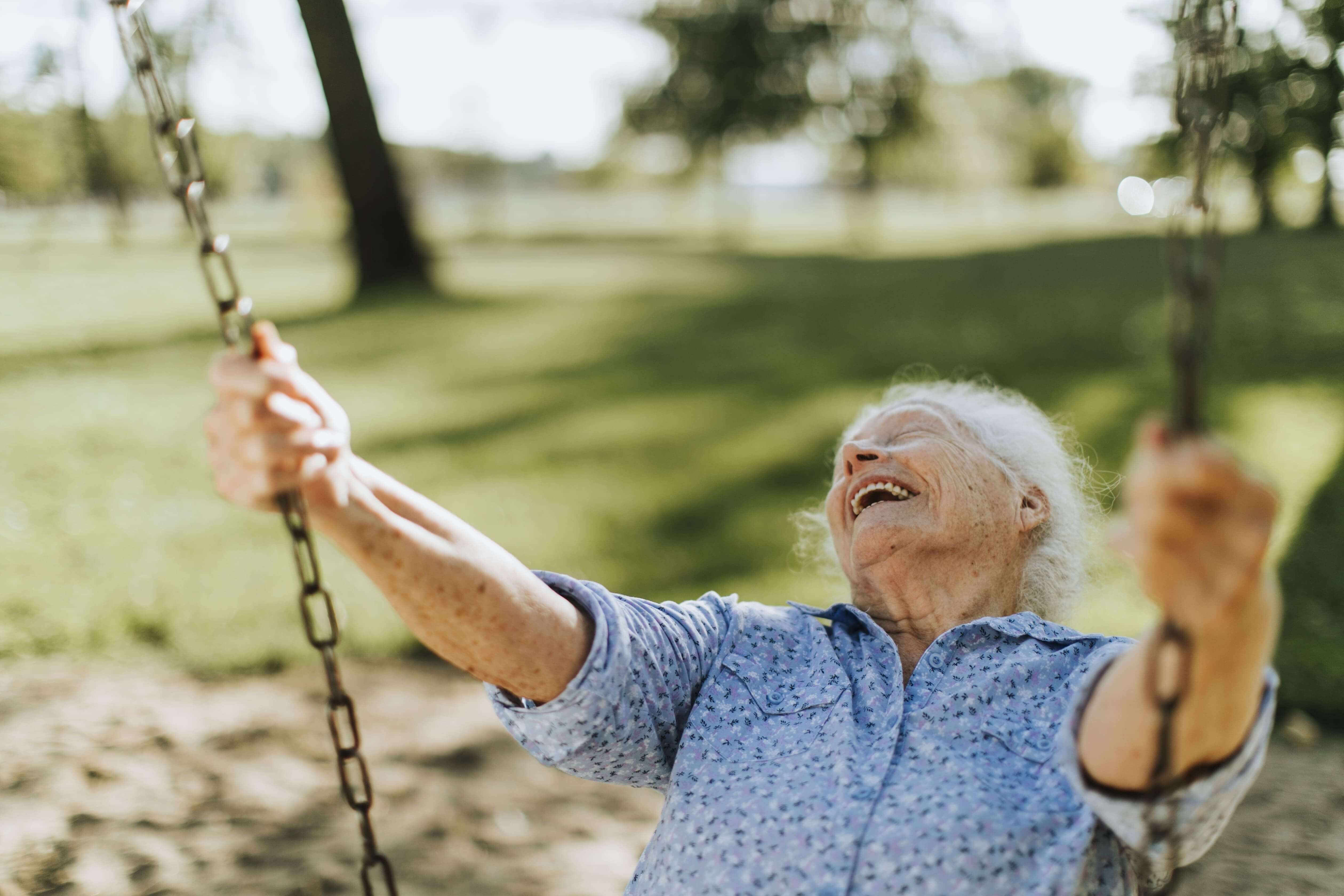 Older woman playing on a swing and laughing