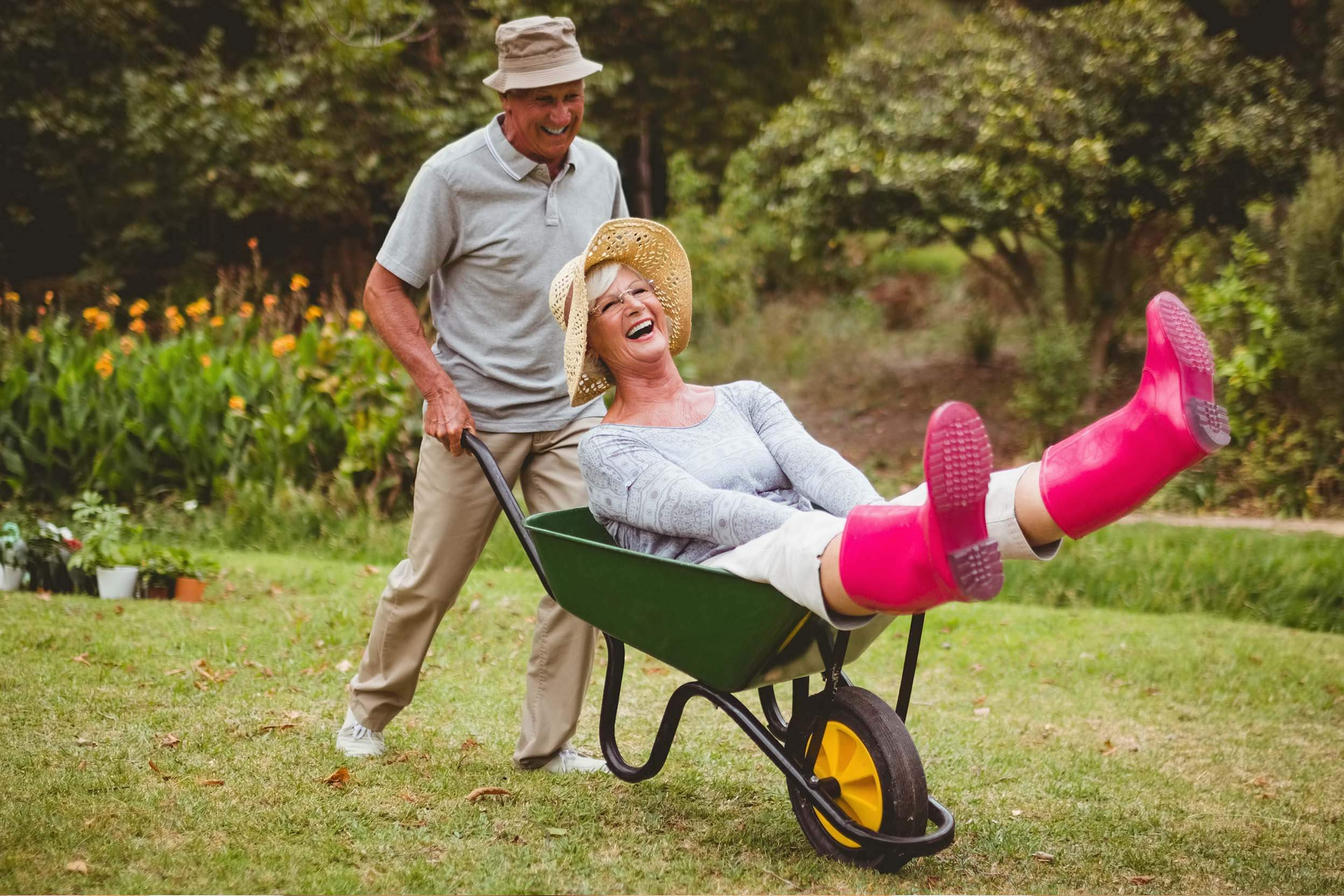 An older man laughing and pushing his happy wife around in a wheelbarrow