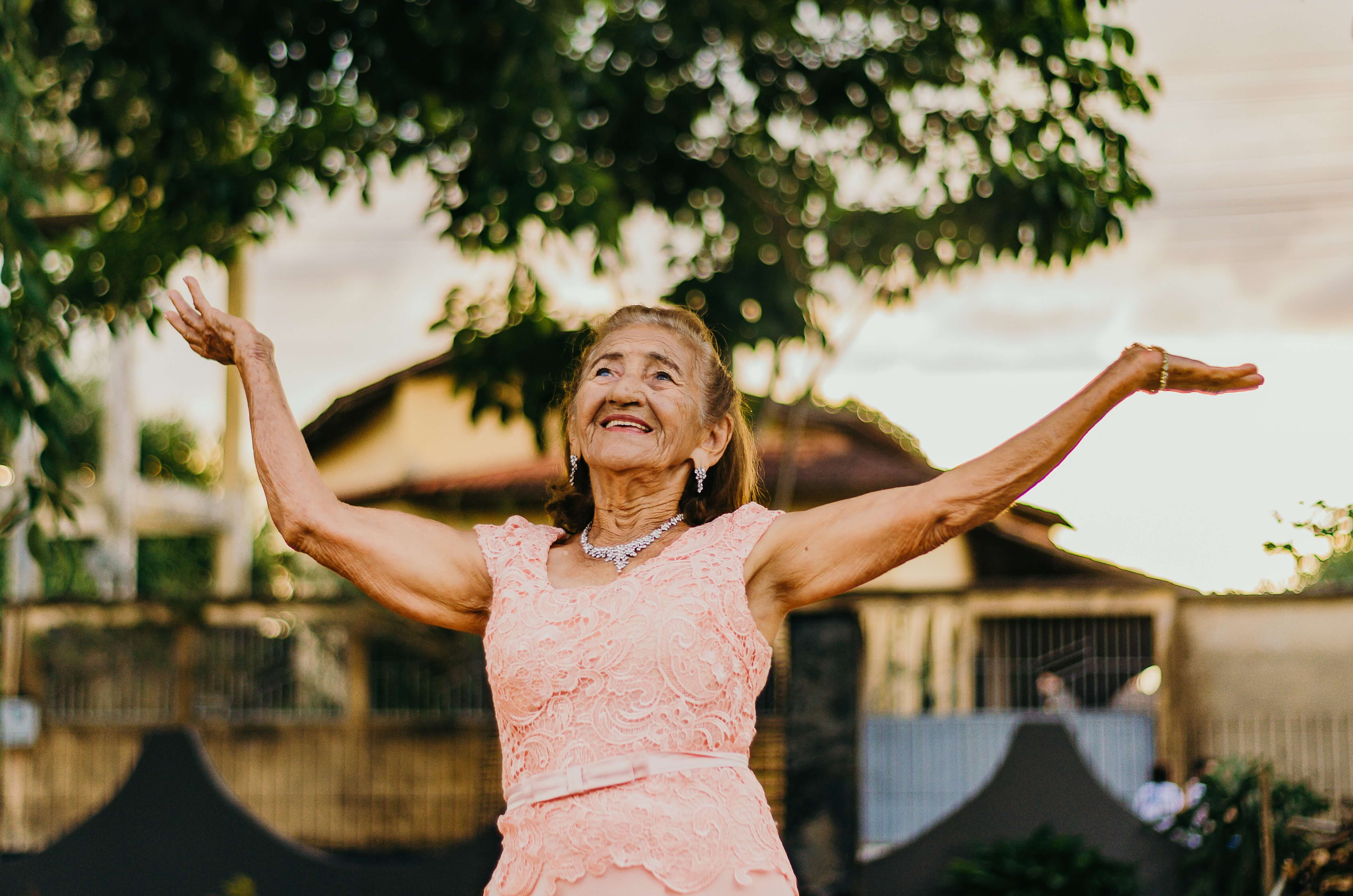 Elderly woman with arms raised to the sky