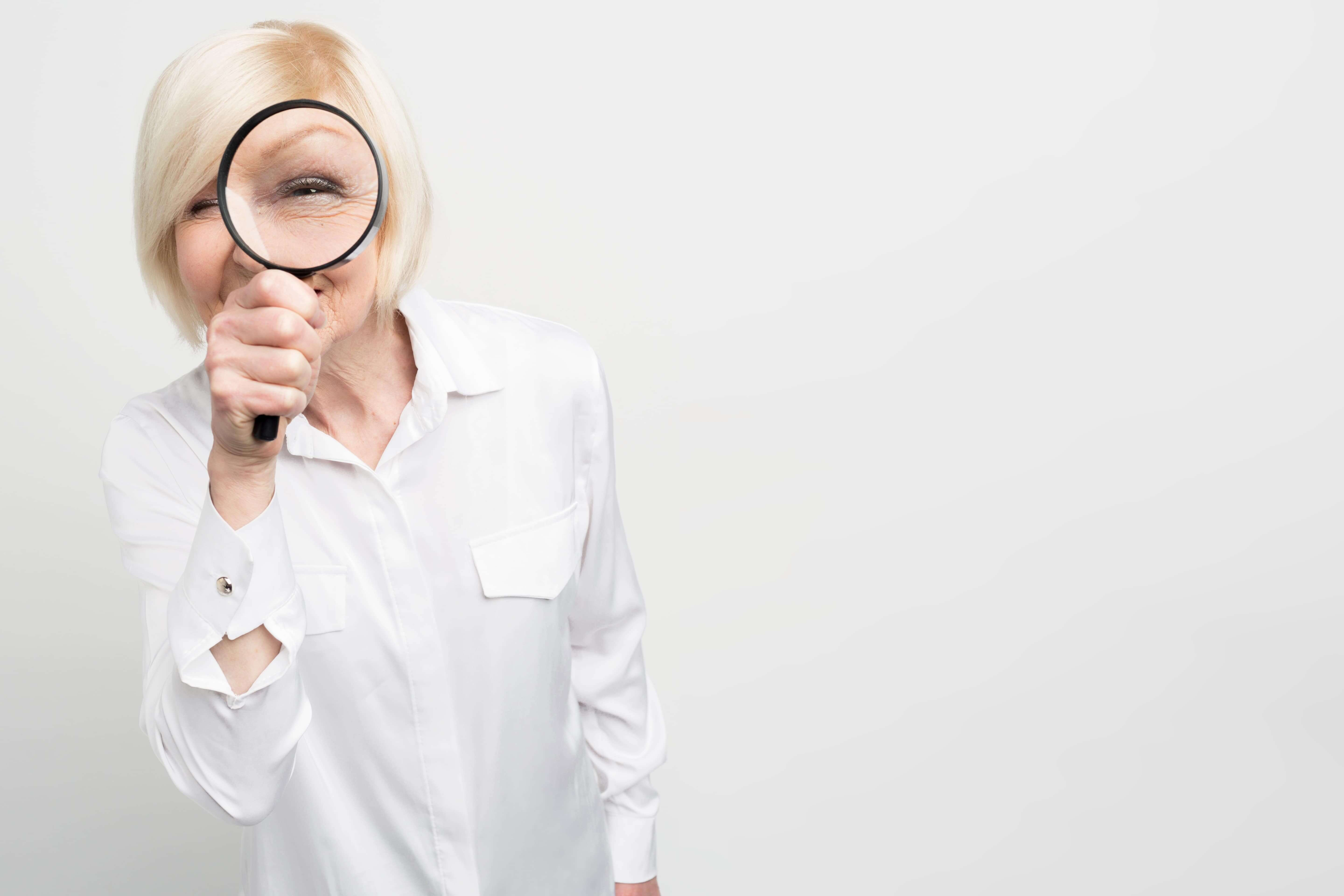 Older woman inspecting holding a magnifying glass up to her eye