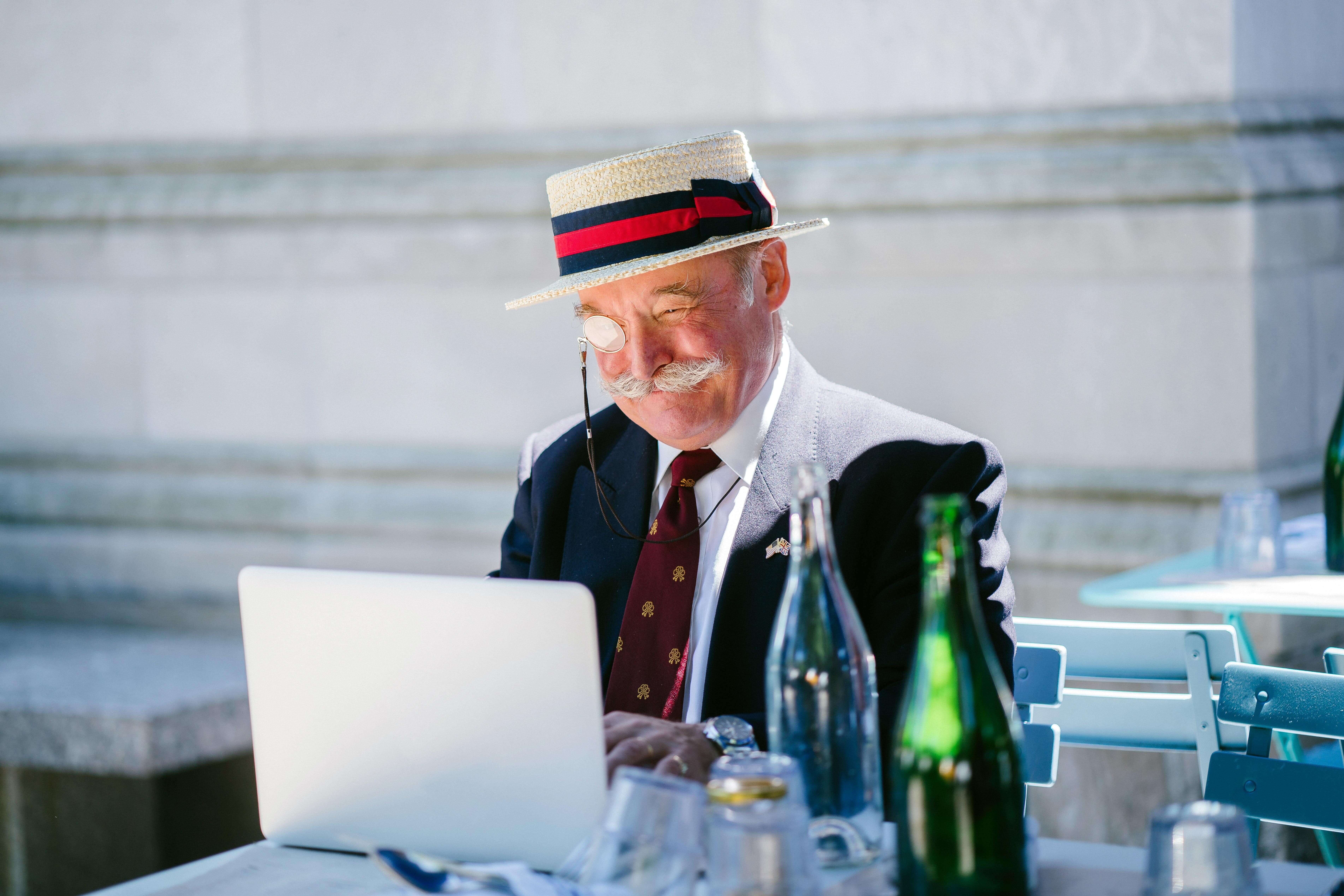Man wearing a bowler hat and magnifying glass on laptop