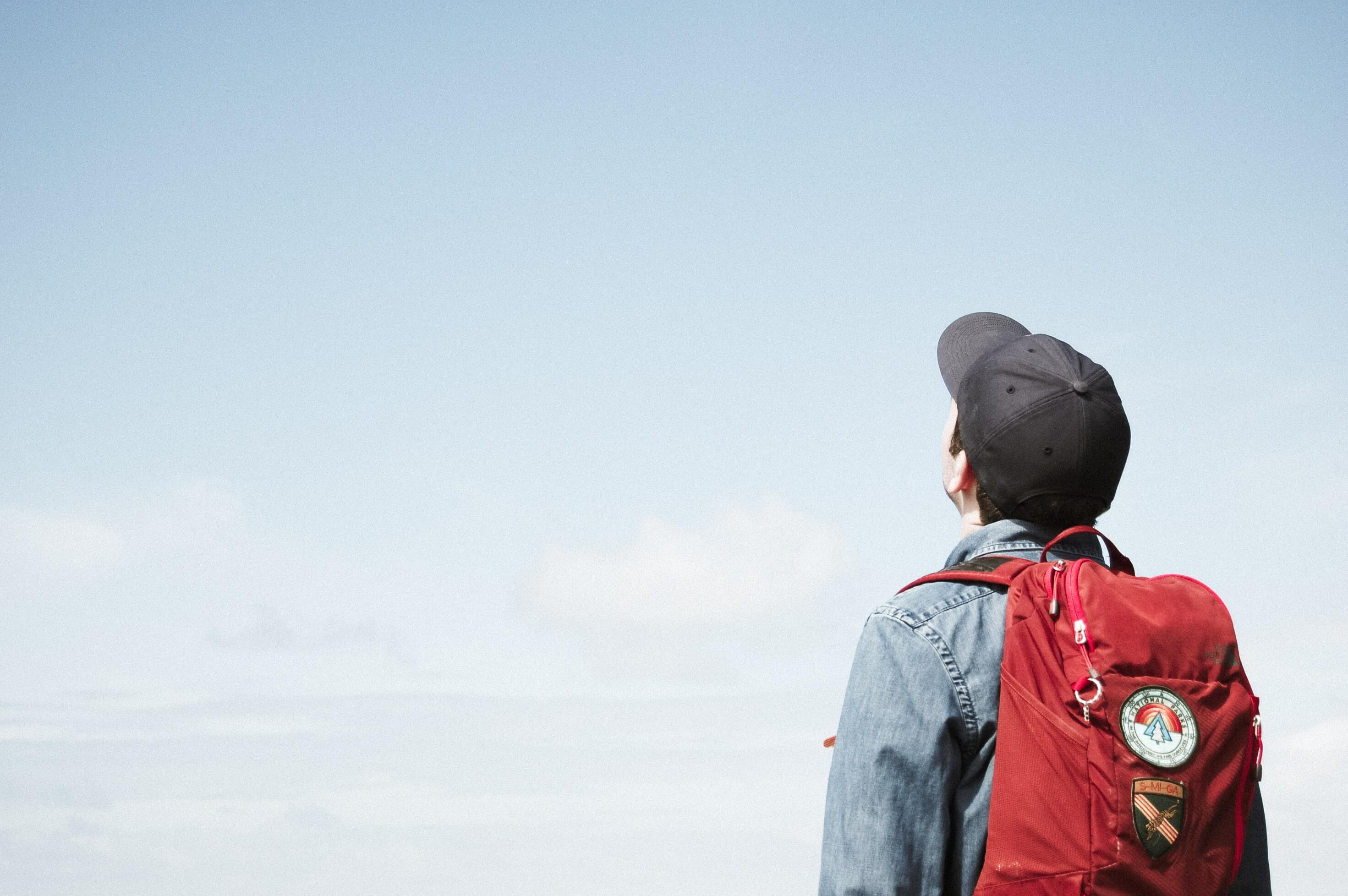 Teenage boy wearing a backpack and staring at the sky