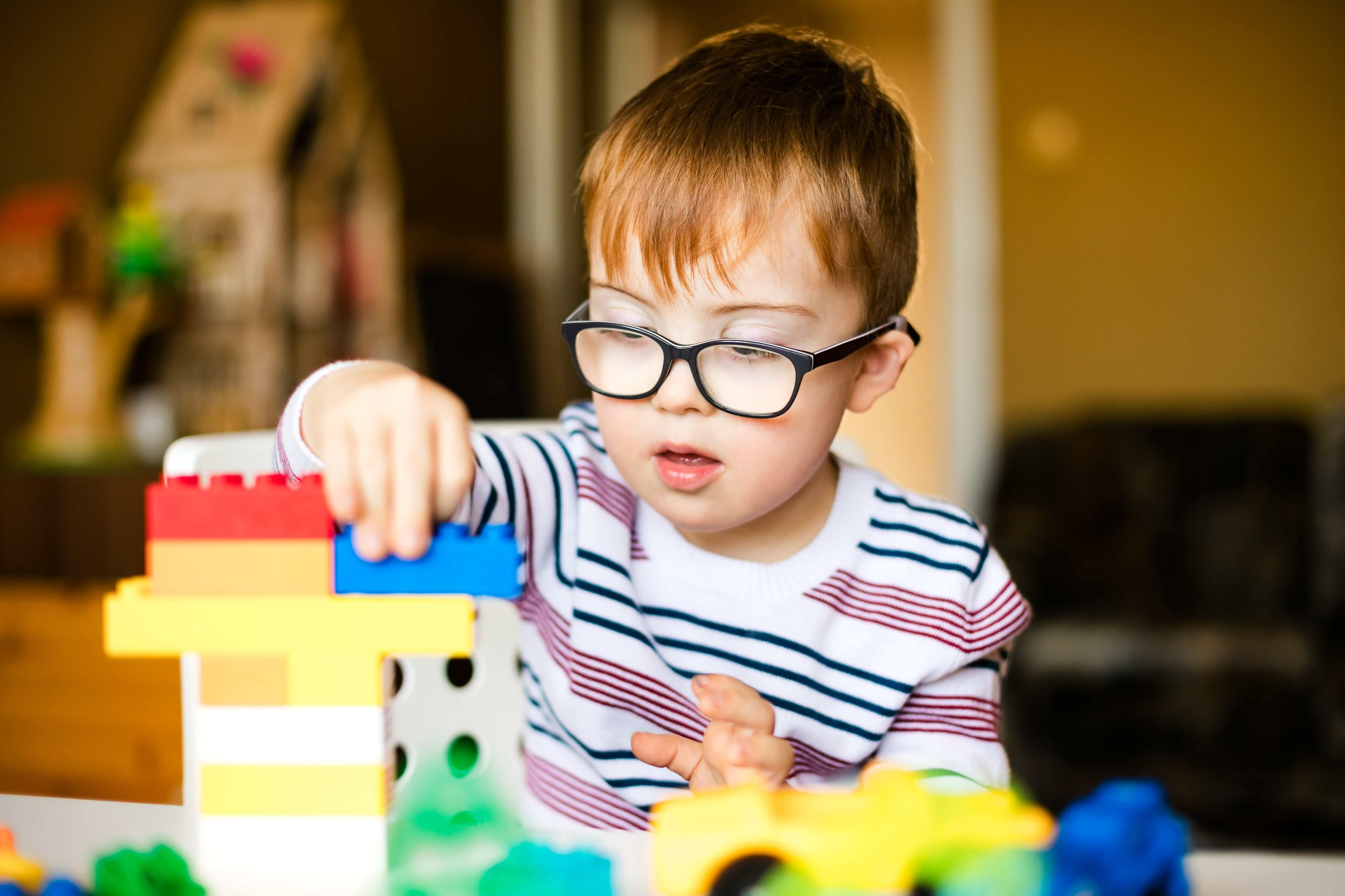 Young boy playing with coloured building blocks