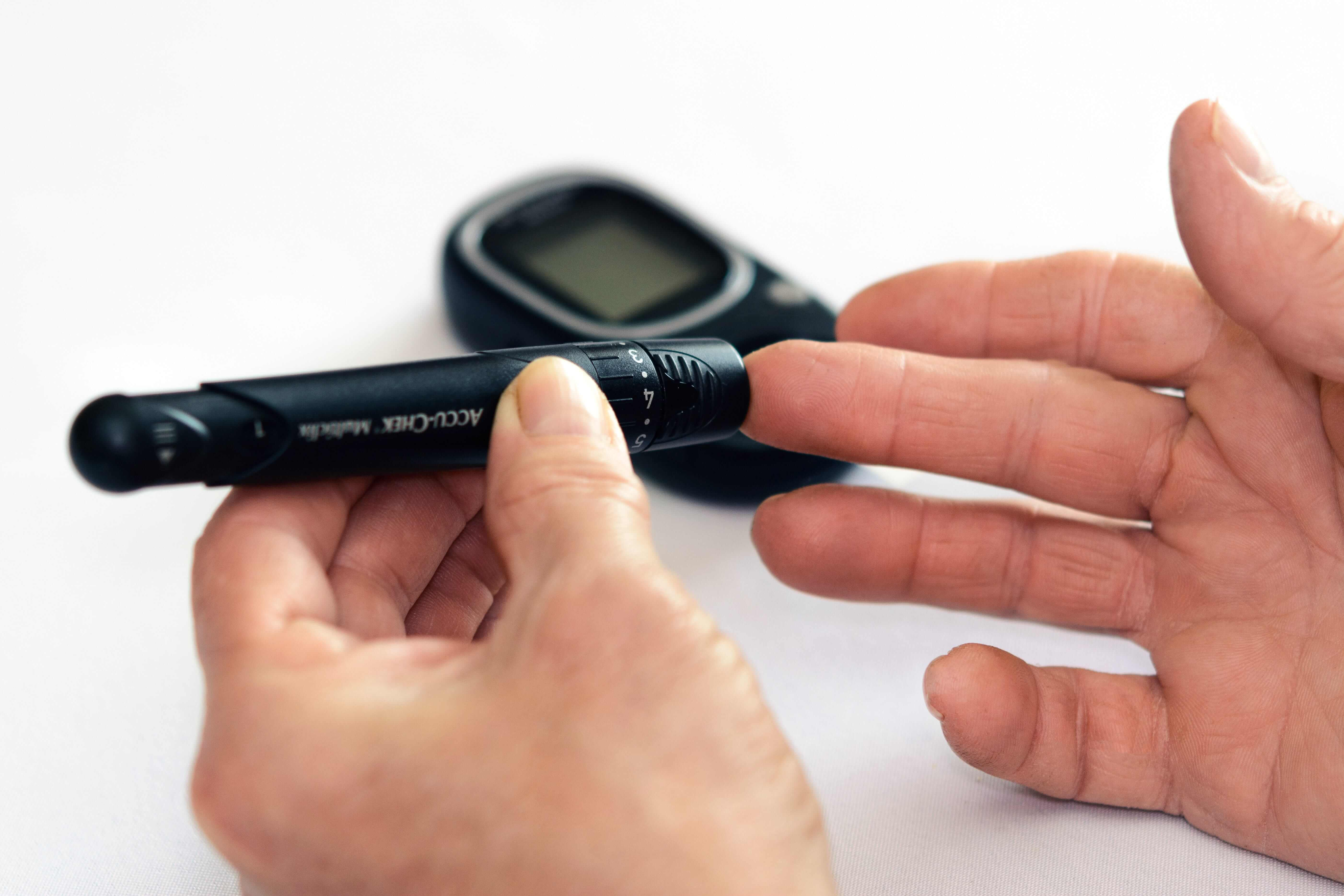 A lancet device being used on middle finger to test blood glucose