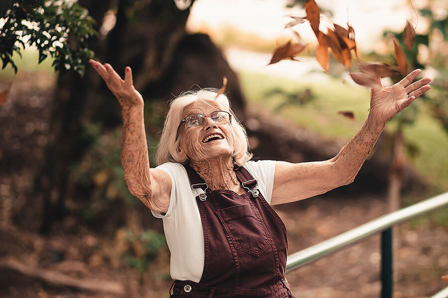 Senior lady in brown overalls throwing autumn leaves into the air