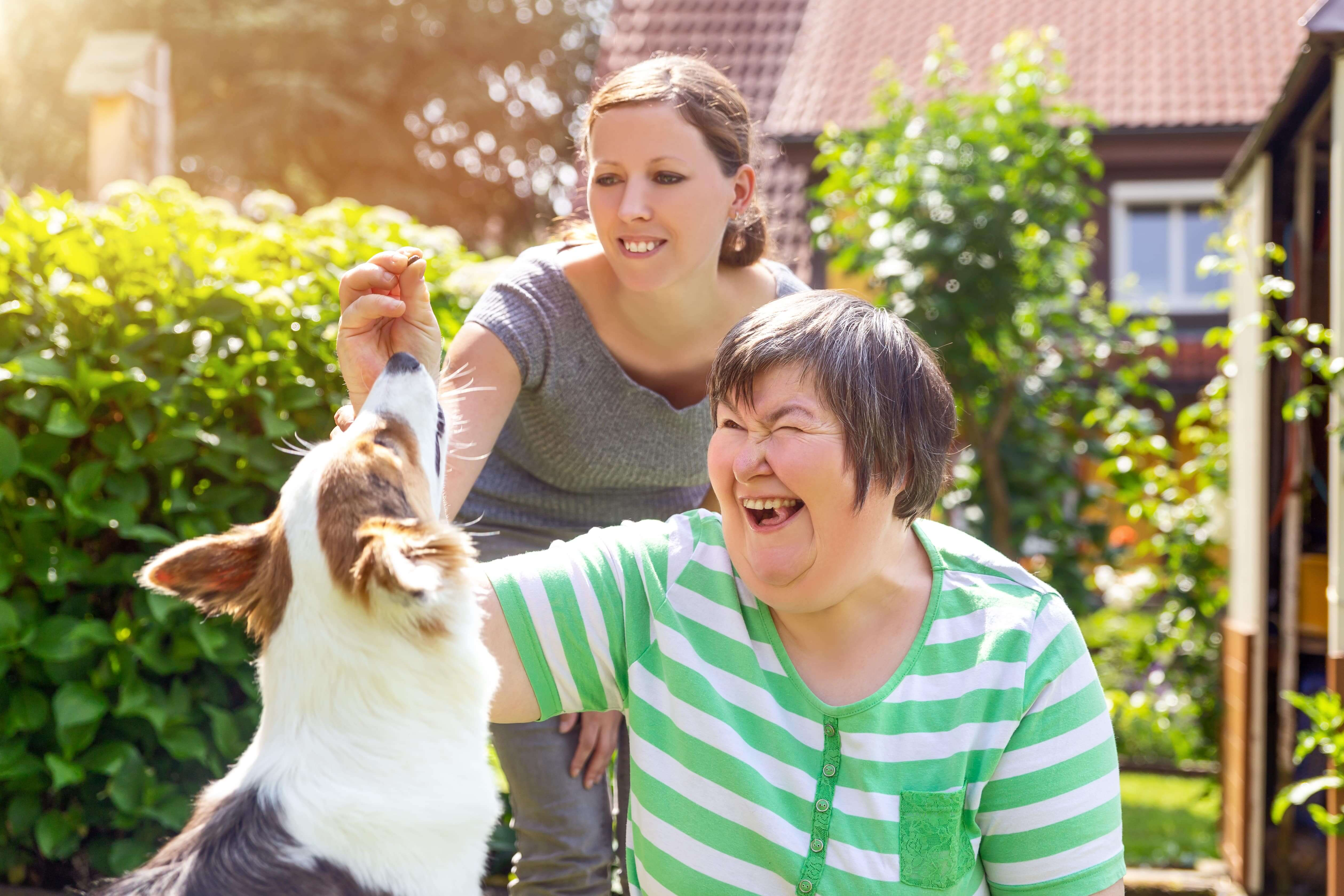 Disabled older woman playing in the backyard with her dog and younger woman