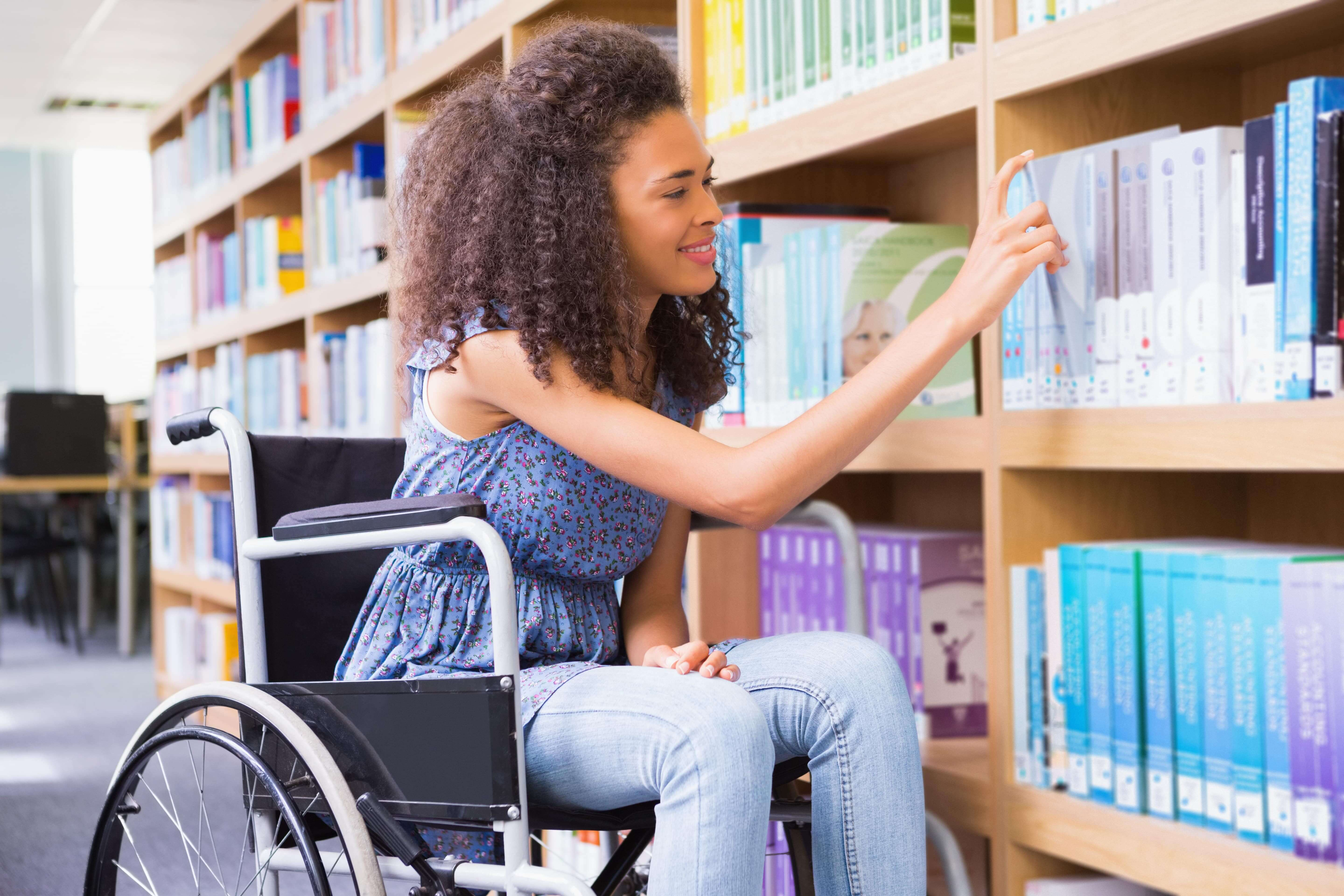 Young woman in a wheelchair selecting a textbook in a university library