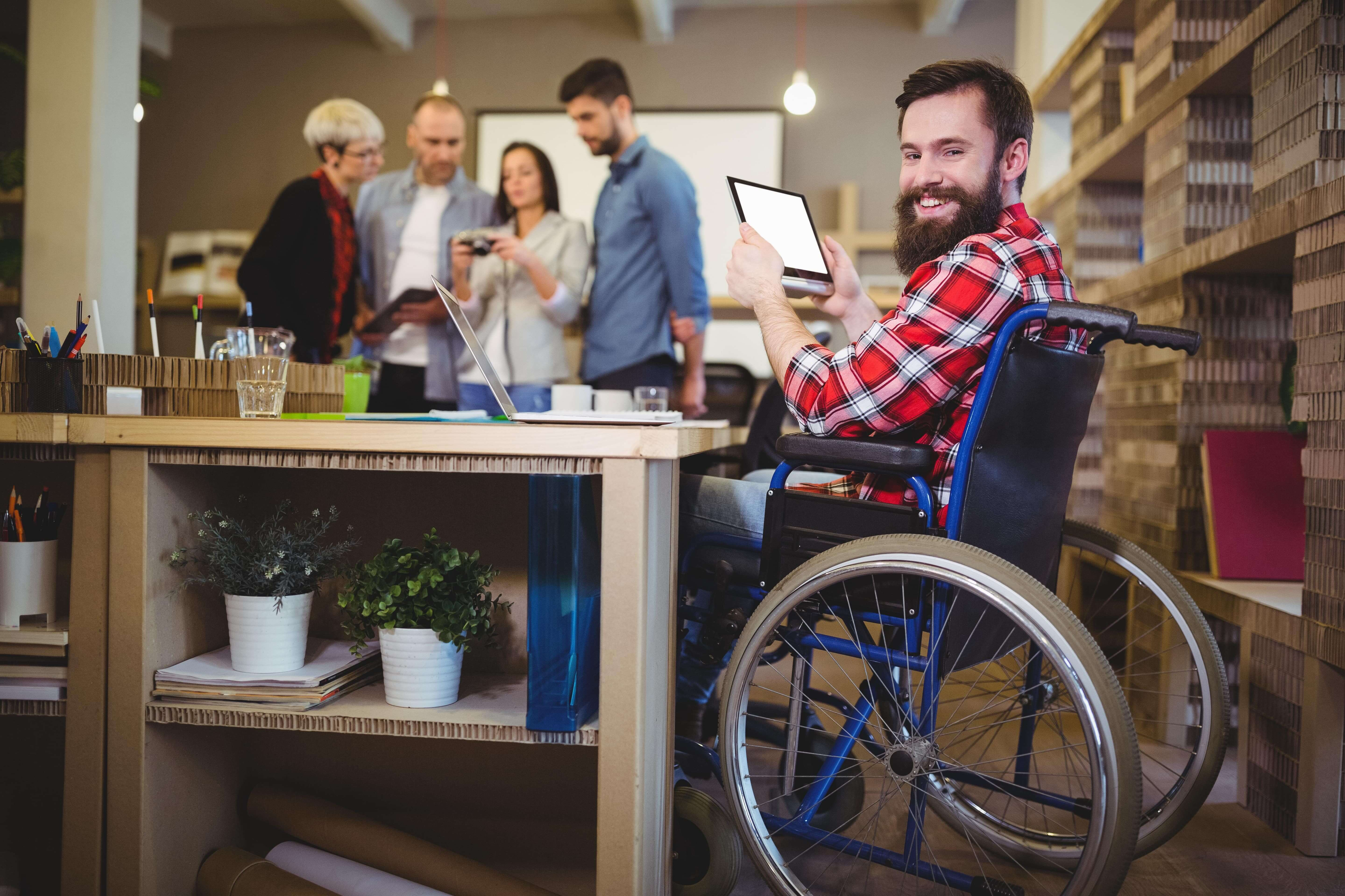 Young bearded man in a wheelchair using a tablet