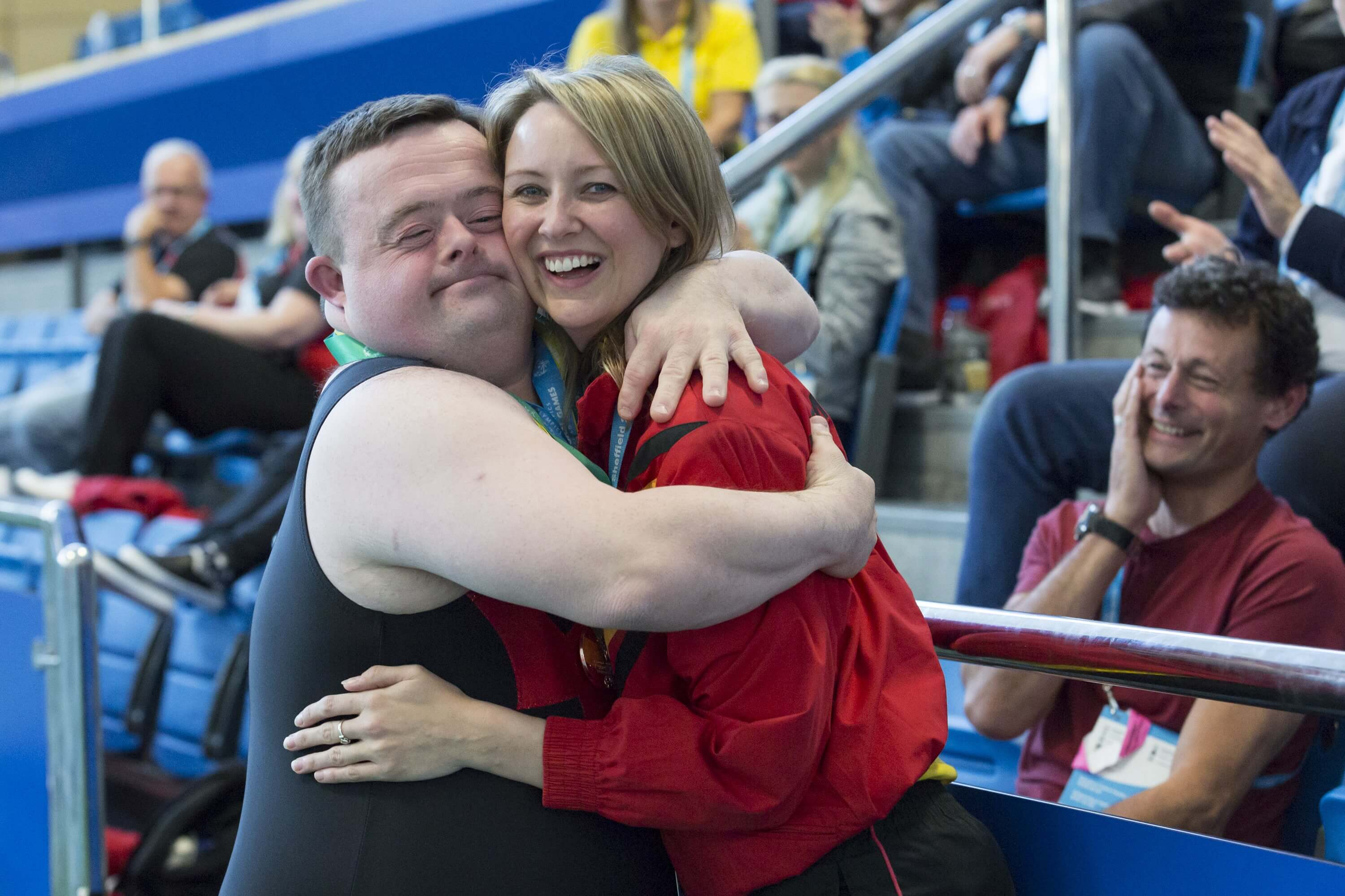 Smiling man with Downs Syndrome hugging happy young woman