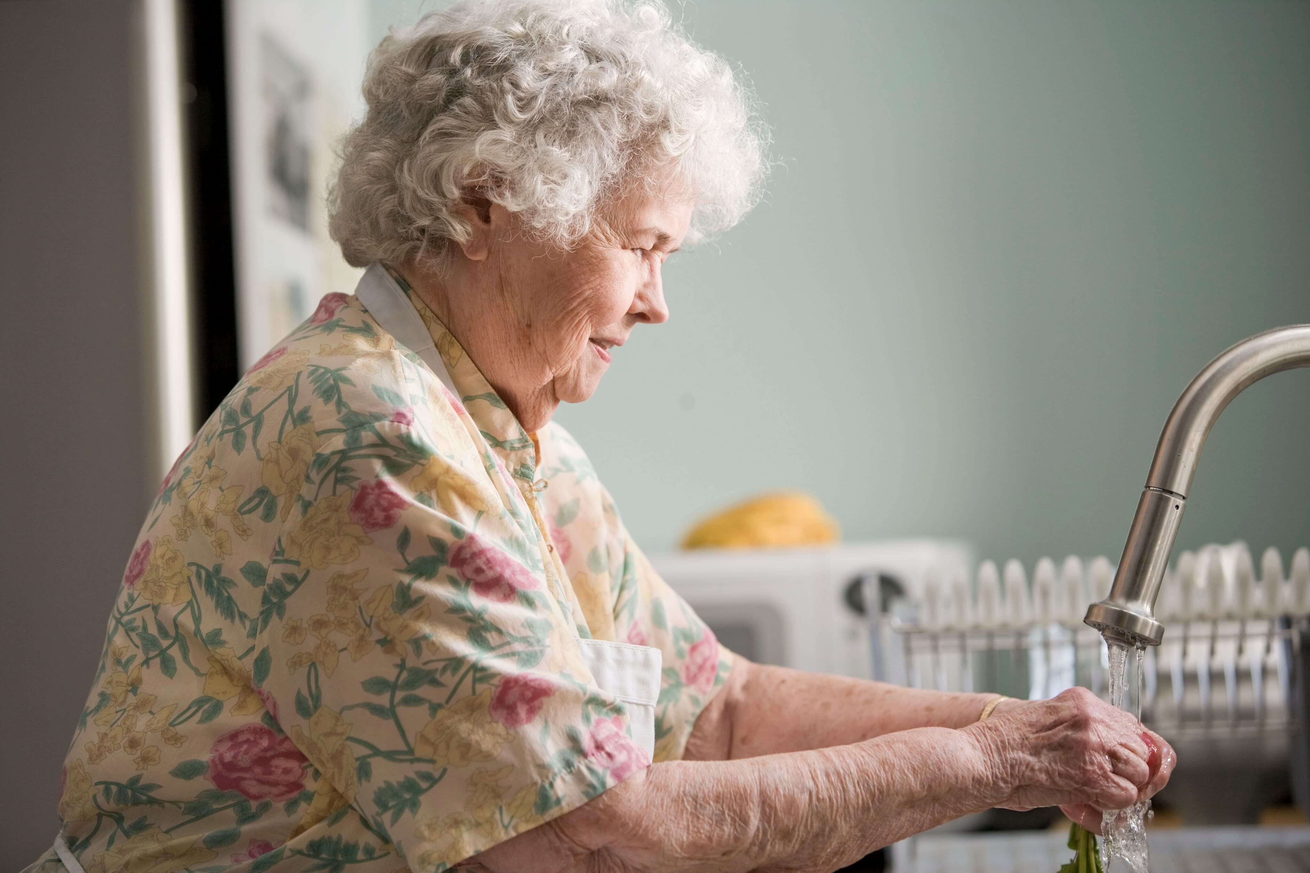 Senior woman washing her hands at the kitchen sink