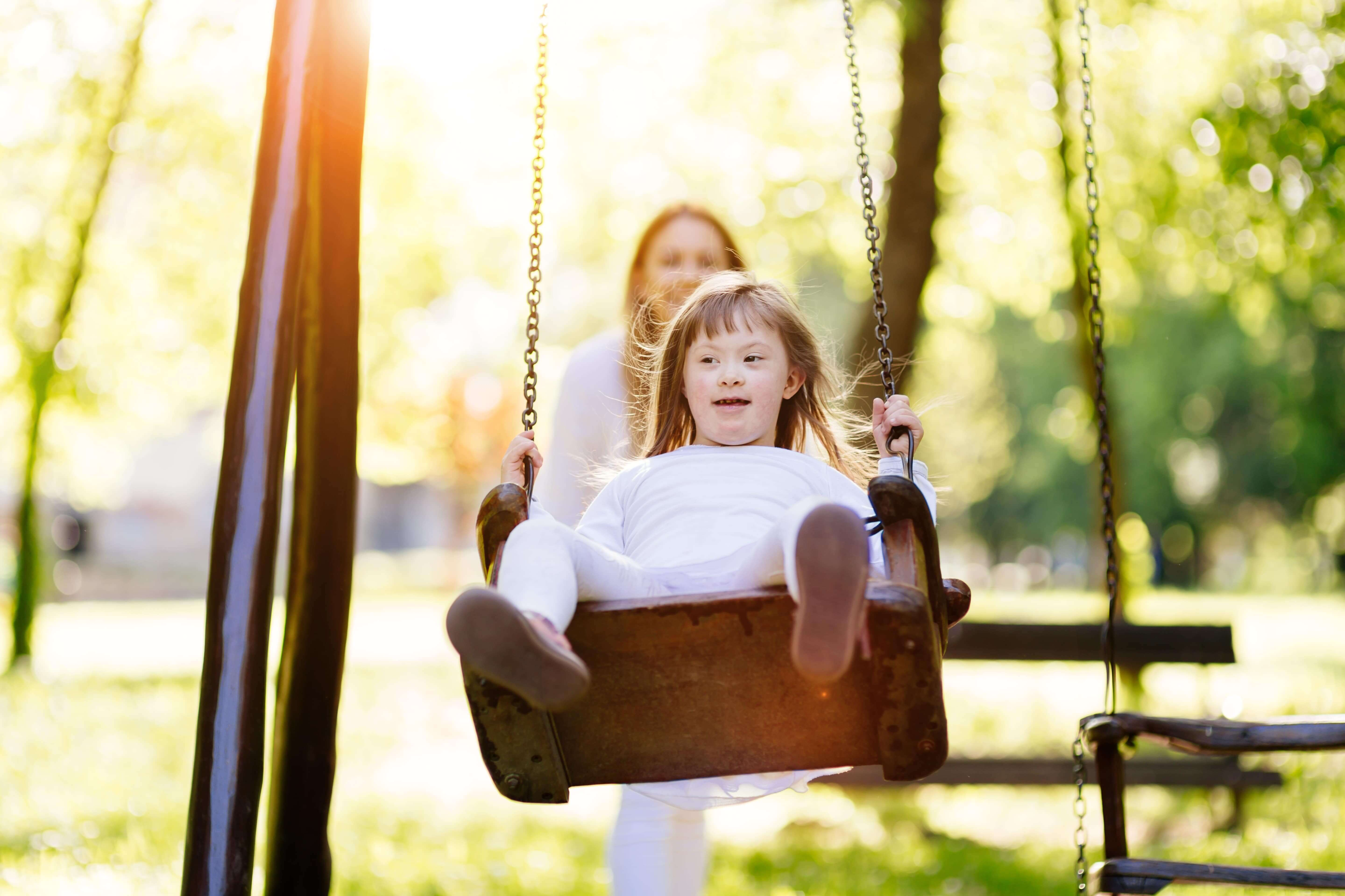 A young girl with Downs Syndrome playing on a swing