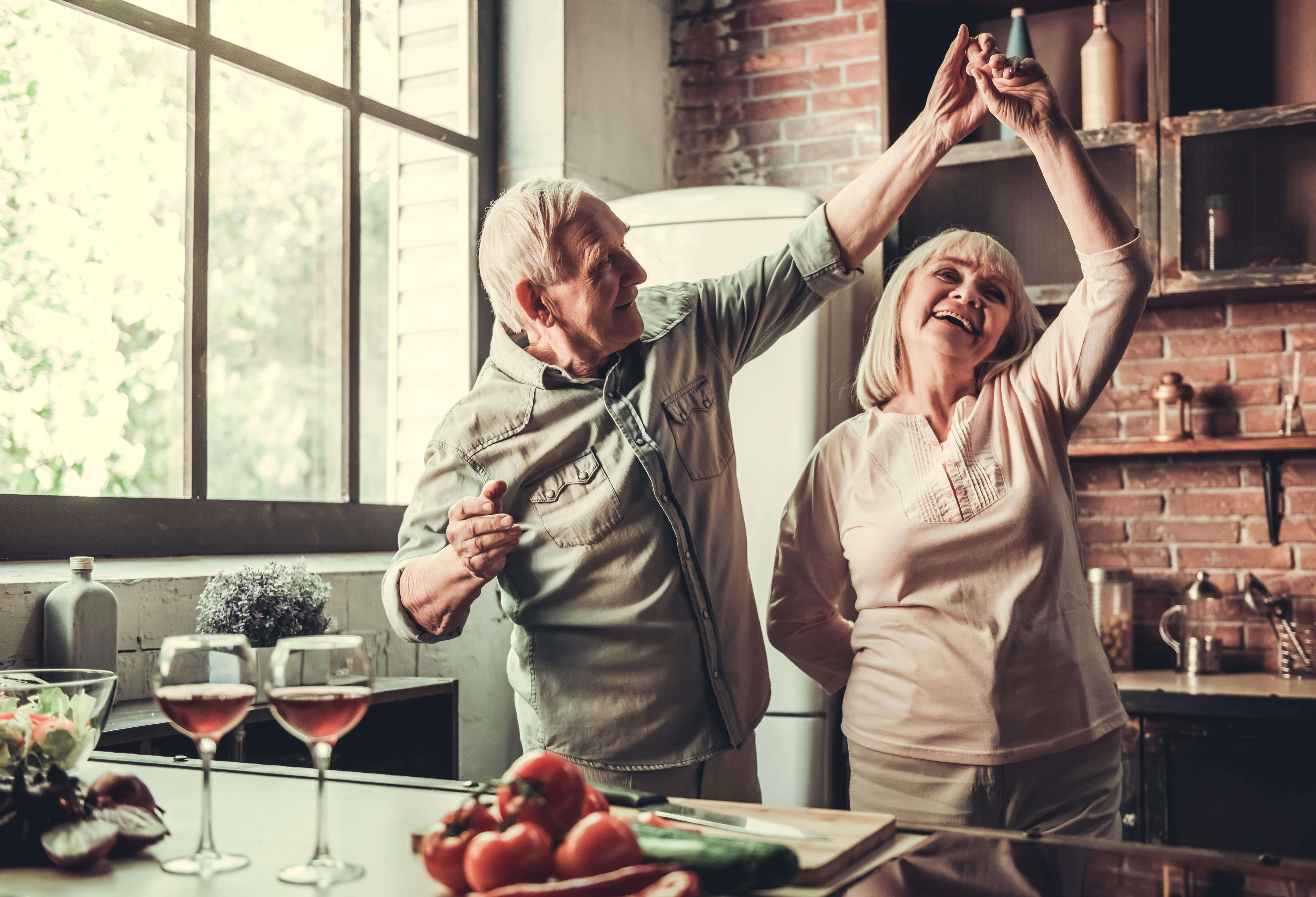 Senior couple dancing together in their kitchen