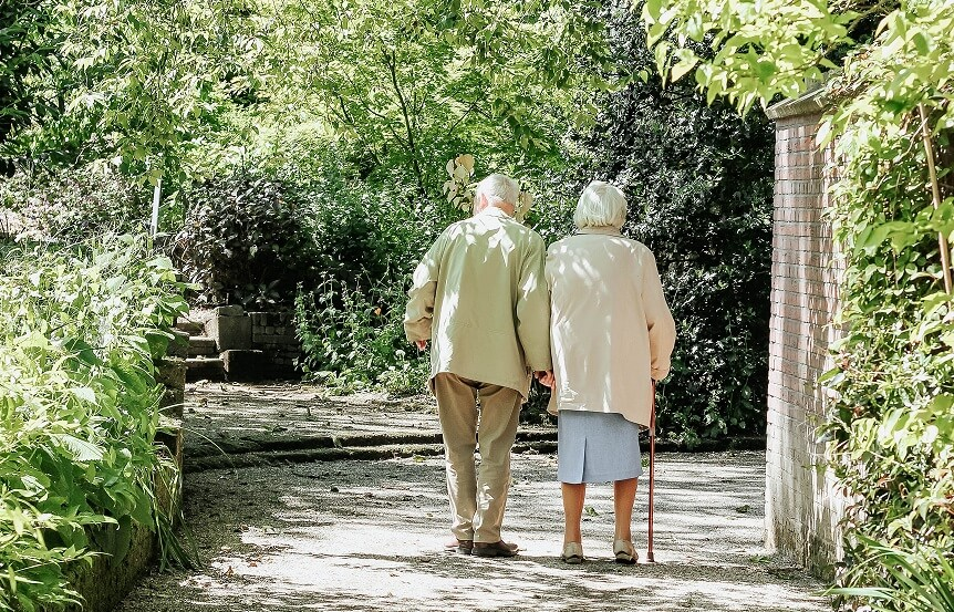 Senior couple walking through gardens