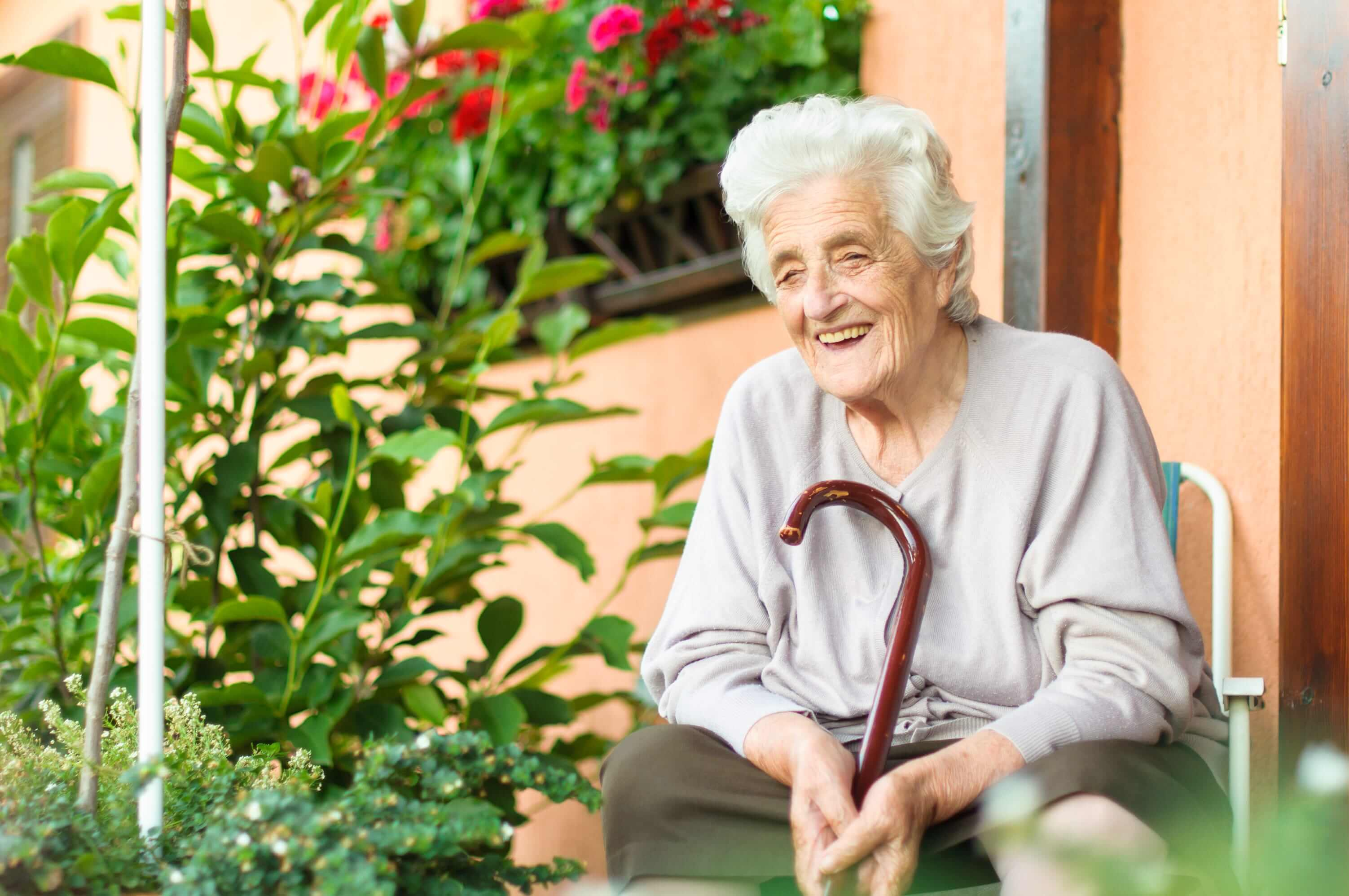 Senior woman with a walking stick sitting in her garden