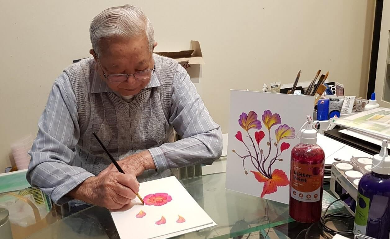 Vietnamese man painting watercolour flowers in his home