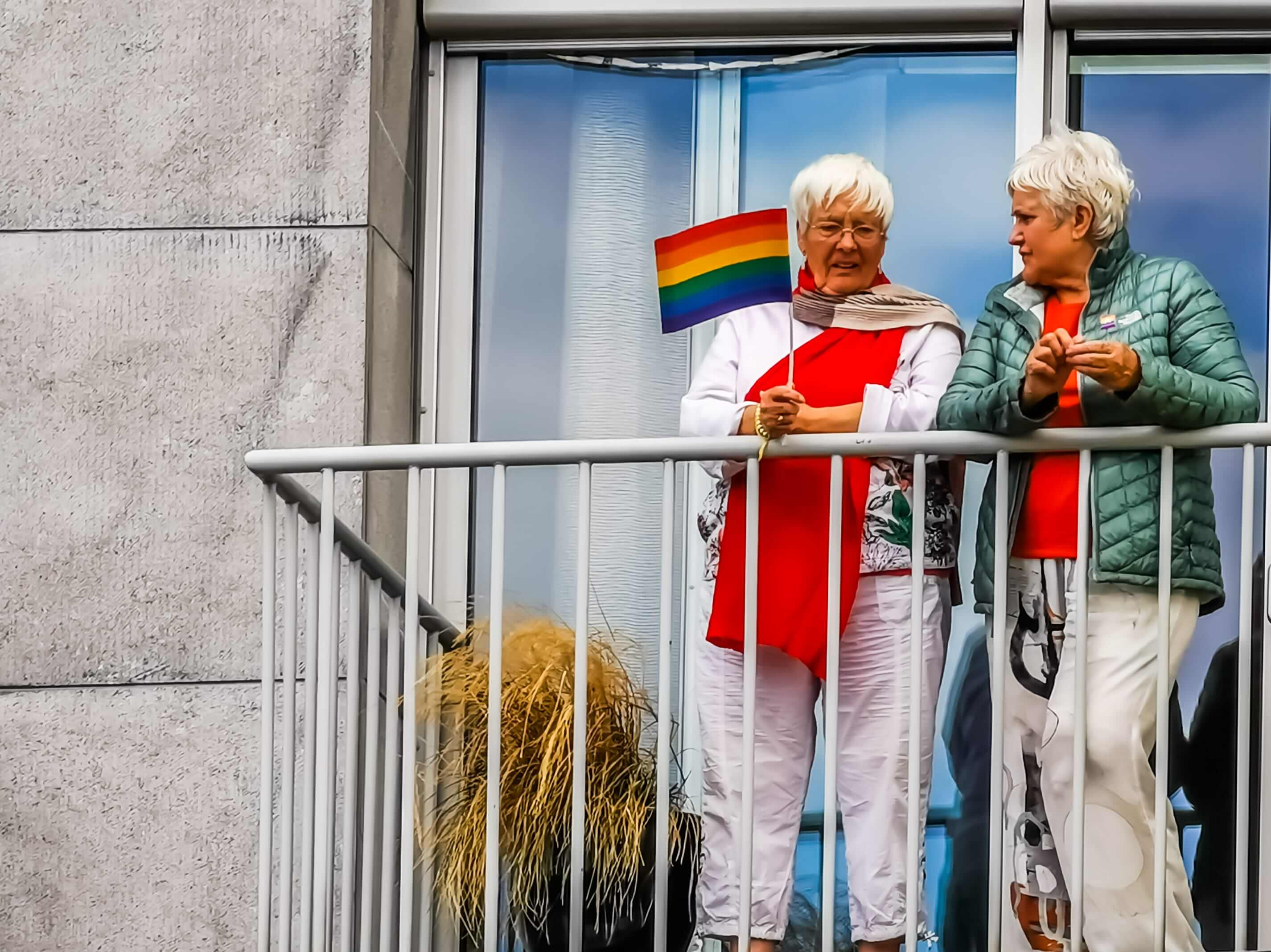 Senior same-sex female couple on a balcony with a rainbow flag