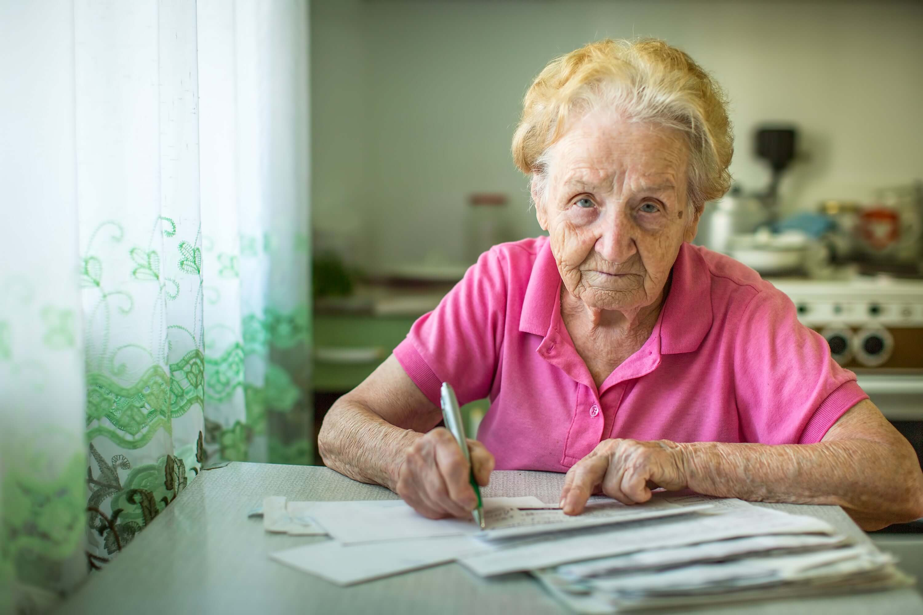 Elderly lady sitting at her dining table paying her bills