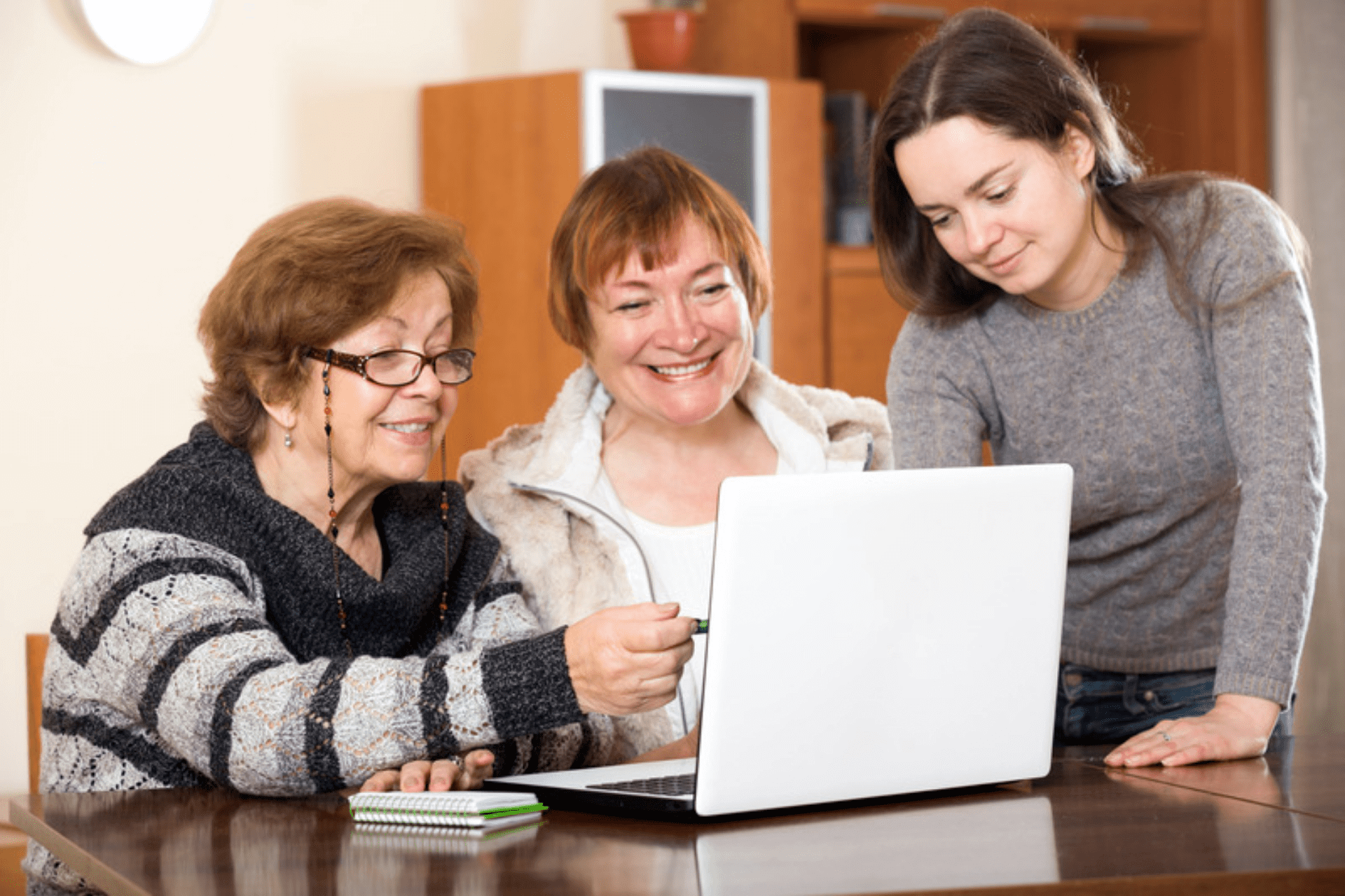 Three generations of women sitting at a table viewing a laptop